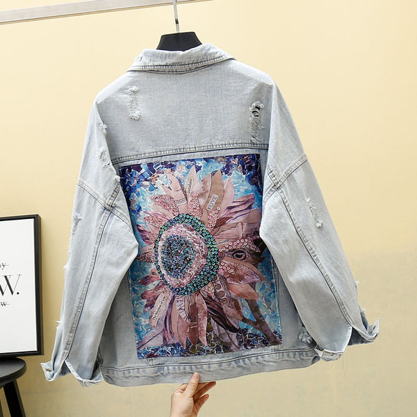 Ένα trendy γυναικείο τζιν μπουφάν με ένα πολύχρωμο εκτύπωσης και σχισμένα μοτίβα